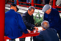 Chinese men playing mahjong, near the Temple of Heaven in Tiantan Park, Beijing, China