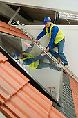 Checking a photovoltaic panel on the roof at the Able Skills Training Centre, Dartford, Kent.