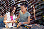 "Berkeley CA Preteen girls experimenting with carpentry at local ""discovery park"" for free-form activities  MR"