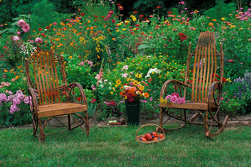 Two handmade chairs at the edge of a blooming country garden, Midwest USA