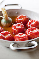 Detail of a simple dish of roasted whole tomatoes cooked with a bulb garlic