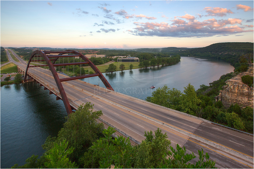 Taken from the southeast side of the 360 Bridge that spans the Colorado river, this Austin image shows the view at sunrise on an early June morning. In the distance, thunderclouds roll across the Texas Hill Country and the full moon falls into the horizon.