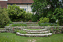 Edwin Lutyens steps, Great Dixter. Planted with pink and white fleabane daisies (Erigeron karvinskianus), Red valerian (Centranthus ruber) and blue Silene coeli-rosa 'Blue Angel'. The tree on the right is an old Mulberry.