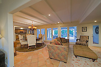 Spanish family room featuring white painted bemed cielings, elegant furnishings, tile floors and large windows.