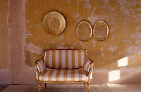 A Louis XVI canape upholstered in striped silk with a calligraphy sceen print stands against a distressed wall decorated with objects covered in gold foil