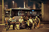 Italy. Lazio region. Rome. Romanian men sit on a concrete block while waiting at Tiburtina railway station to receive at nighttime a free meal from Caritas. Some men have daily jobs as construction workers, others don't have any jobs at all, nor a place to sleep. They talk about social issues and politics. Romanian immigration. Public bus in Tiburtina bus station. 26.09.2011 © 2011 Didier Ruef