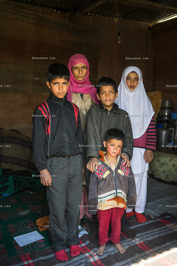 (Alison Griffin to fill in names) (L-R) (elde son, mother, younger son, youngest son, and daughter) poses for a family portrait inside their temporary shelter built next to their collapsed home in Abikarpora village on the Dal Lake, Srinagar, Jammu and Kashmir, India, on 25th March 2015. Since the flood, (mother) has been widowed, and is left with four young children and no home. Her family now lives in a temporary shelter built using the emergency shelter kit, and continues their recovery with the help of relief kits such as education kit, food basket, hygiene kit and non-food items from Save the Children. Photo by Suzanne Lee for Save the Children