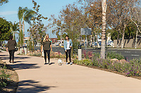 Two women walking a small white dog walk towards the camera while another woman walks away from the camera along the Harbor Boulevard Cornerstone Bike Trail in Costa Mesa, California under a clear blue sky.  The landscaping of the path, including a diversity of plants and rocks, can be seen behind and beside the people.  The landscape architecture work on the project was done by David Volz Design.