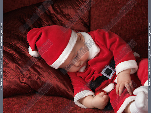 Six month old baby boy in Santa costume sleeping on a sofa with a Christmas bauble in his hand