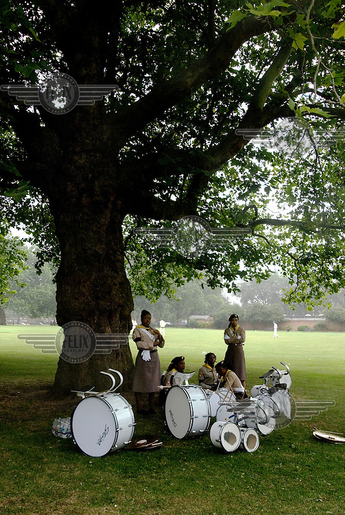 Members of the Pathfinders, a youth group within the Seventh-Day Adventist Church, shelter from rain beneath a tree, in London Fields, a park in the London Borough of Hackney.