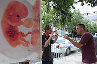 CHARLOTTE, NC - September 4, 2012 - Button vendor Robert McCallum (left) argues with an antiabortion protester on the street outside the Charlotte Convention Center. <br /> <br /> &quot;It's pornography,&quot; argued McCallum to the protester in regards to the huge signs antiabortion protesters are carrying down the streets in Charlotte. <br /> <br /> &quot;You can't have a civil discourse with them,&quot; he said after walking away, &quot;If your showing images that are violent images and there are little children out here to me that is pornography.&quot;