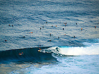 A surfer rides a wave at Maui's Honolua Bay while other wait for the next set.
