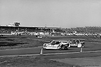 DAYTONA BEACH, FL: The Holbert Racing Porsche 962 103 of Al Unser Jr., Derek Bell and Al Holbert is driven on the infield road course ahead of the March 85G 5/Porsche of Bill Whittington, Randy Lanier and Al Leon during the 24 Hours of Daytona on February 3, 1985, at the Daytona International Speedway.