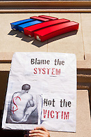 "A protester in the Occupy Orange County, Irvine march on November 5 holds a ""Blame the system, not the victim"" sign in front of the Bank of America logo in Irvine, CA."