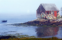 USA, Maine, Lands End, lobster shack with lobster bouys perched on a rocky shoreline with the ocean in the background