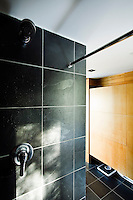 A walk-in shower has walls and floor covered in black slate tiles