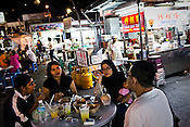 Locals of different ethnicities gather to eat a Chinese Hawker stall in the UNESCO heritage city of Georgetown in Penang, Malaysia. Photo: Sanjit Das/Panos