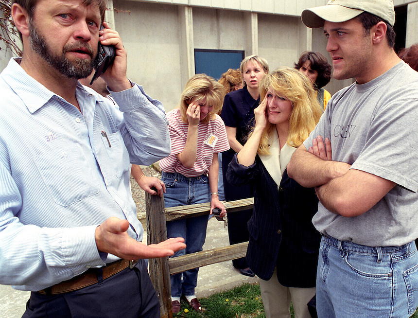 Bill Curry, left, talks on the phone with family after getting word by cell phone that his daughter Kendra and niece Kami had barricaded themselves in a closet with over 20 other students at Columbine High School in Littleton, Colo., during the April 20, 1999, shootings. At center, mother Lorie Curry (right) and an aunt of both girls Janet Olmstead cry at the word that the girls were still in the gun-shattered school. At far right Jason Curry, brother of Kendra waits by their sides..