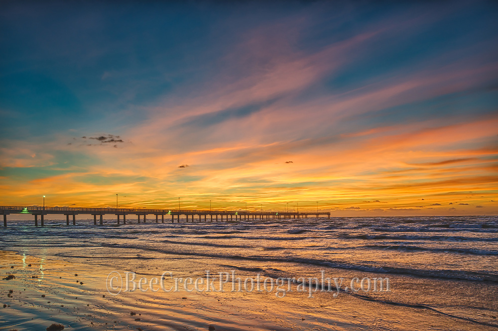 Another great sunrise on the beach on the Texas Coast in Port Aransas where the surf was calm and the skies were full of vivid colors this day with the Caldwell fishing pier in the distance.