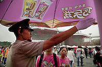 China. Shanghai. World Expo. Expo 2010 Shanghai China. Outside Switzerland Pavilion. A policeman shows the way to a couple of chinese tourists. Pink ice cream sunshade with drawings and chinese writings used for advertisements. Pink T-Shirts with elephants. White glove and cap. Cloudy sky. 27.06.10 © 2010 Didier Ruef