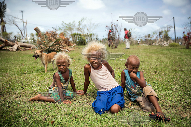 L-R: Two year old Janou with her eight year old sister Belonet and four year old brother Alfred. Their garden, where they grow food, was destroyed by Cyclone Pam on 13 March 2015. They came with their father to a local grocery shop on outskirts of Port Vila to receive bags of rice being distributed as aid.