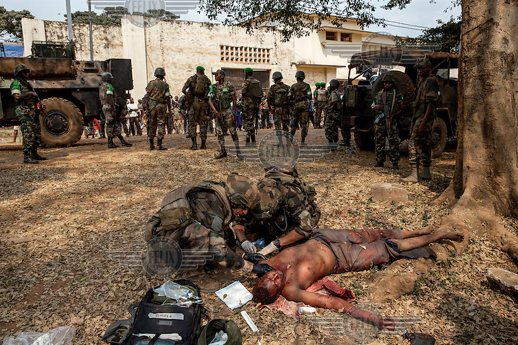 A man, covered in his own blood, is treated by soldiers. He was attacked by a Christian mob who accused him of being a member of the Seleka. Although he was saved from the mob by French peacekeepers he died from his wounds. In 2013 a rebellion by a predominantly Muslim rebel group Seleka, led by Michel Djotodia, toppled the government of President Francios Bozize. Djotodia declared that Seleka would be disbanded but as law and order collapsed the ex-Seleka fighters roamed the country committing atrocities against the civilian population. In response a vigillante group, calling themselves Anti-Balaka (Anti-Machete), sought to defend their lives and property but they then began to take reprisals against the Muslim population and the conflict became increasingly sectarian. French and Chadian peacekeeping forces have struggled to contain the situation and the smaller Muslim population began to flee the country.