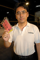 """Referee Shinsuke Funabashi. He is holding a card saying """"break"""" which he uses during bouts involving wrestlers with hearing disabilities."""