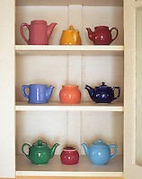 USA, Antique ceramic teapots & sugar bowls in cupboard.
