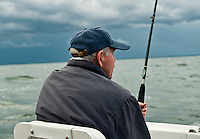 Man sport fishing from a boat.