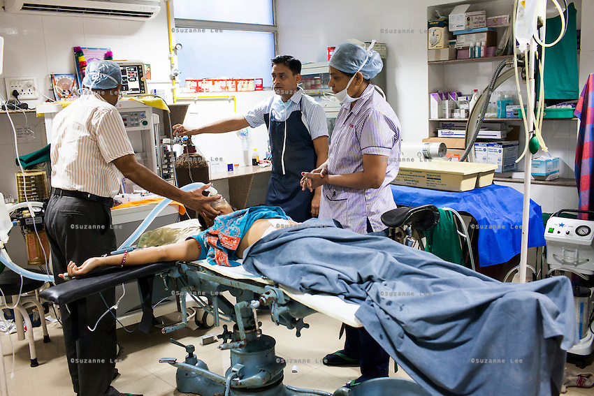 Doctors prepare to move the patient to the recuperation room after performing a hystroscopy, a pin-hole operation, on her in the operation theater of Akanksha IVF and Surrogacy Clinic in Anand, Gujarat, India on 11th December 2012. Photo by Suzanne Lee / Marie-Claire France