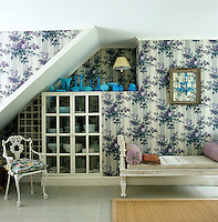 A fabric of life-size bouquets of lilac covers the walls of the dining room and a built-in china cupboard and wine rack make good use of the space under the stairs