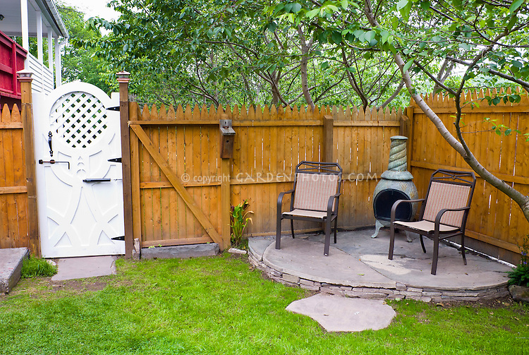 Firepit bbq fireplace outdoors on small garden stone patio, wooden privacy fency, pretty garden gate next to house, lawn grass, birdhouse, trees