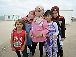 Girls pose on their walk to school in the Zaatari refugee camp near Mafraq, Jordan. Established in 2012 as Syrian refugees poured across the border, the camp held more than 80,000 refugees by early 2015, and was rapidly evolving into a permanent settlement. The ACT Alliance provides a variety of services to refugees living in the camp.