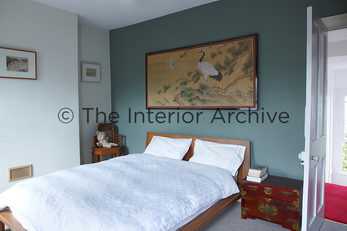 A simple wooden double bed in a blue bedroom with a grey carpet. An ormolu chest is used as a bedside table and the bed linen is white.