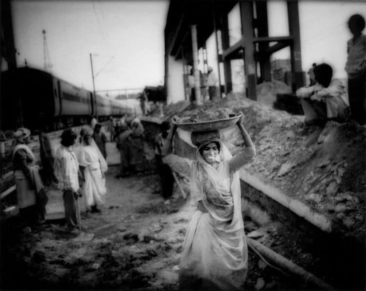 Rajput woman working on and living beside the rails with her extended family in makeshift shelter, New Dehli Station, India.