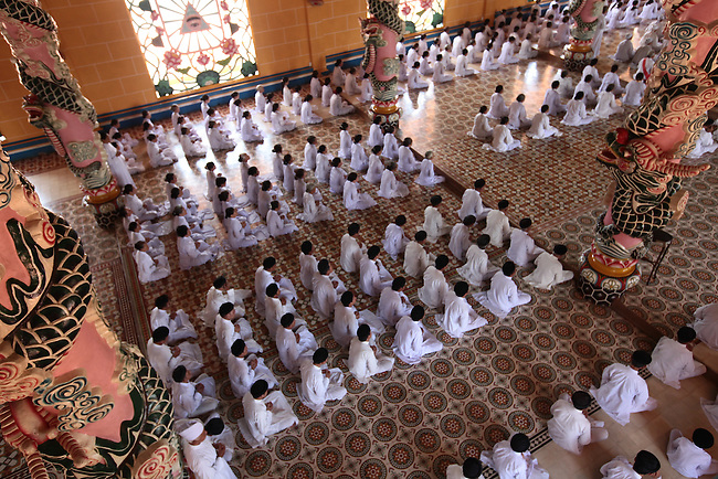 Worshippers kneel during a religious service at the Great Temple of Cao Dai in Tay Ninh, Vietnam. July 2, 2011.