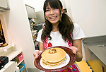 A staffer serves a Hello Kitty pancake during the opening of Hello Kitty's Kawaii (Cute) Paradise, a Hello Kitty theme store, in Tokyo, Japan on Thursday 21 October  2010. .Photographer: Robert Gilhooly
