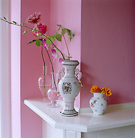 Roses are arranged with simple elegance in antique vases on the living room mantelpiece