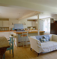 A compact modern kitchen is situated at one end of this open plan living space in an 18th century English home