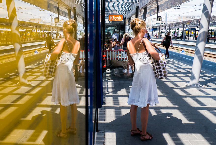 Nederland, Utrecht, 16 aug 2013<br /> Utrecht Centraal Station. Dame in zomers jurkje wacht op het perron op een trein.<br /> Foto(c): Michiel Wijnbergh