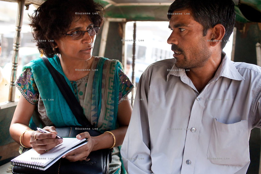 Jagroshan Sharma (aged 36, in grey) discusses work with Dr. Meenal Mehta (in blue), who is in charge of the USAID NSV projects in Ghaziabad, Uttar Pradesh, India, as they wait for a shared rickshaw to leave the village. After doing NSV himself, he has been a star link worker introducing about 5 NSV cases per month since he started working part time under the tutelage of Dr Mehta. Jagroshan had chosen to do a non-scalpel vasectomy (NSV) for many reasons. He wanted to be an equal partner in the relationship, knew that NSV was less complicated and will not put his wife through numerous problems, and wants his two children to do well in life and study in English medium schools despite his modest earnings. Photo by Suzanne Lee / Panos London