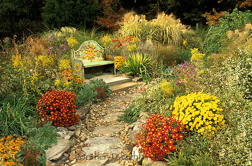 Fall garden with whimsical painted Mexican bench and blooming flowers