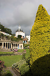 "Portmeirion, in North Wales, is a resort, where no one has ever lived. A self-taught Welsh architect named Sir Clough Williams-Ellis built it out of architectural salvage between the 1920s and 1970s, loosely based on his memories of trips to Portofino. Including a pagoda-shaped Chinoiserie gazebo, some Gothic obelisks, eucalyptus groves, a crenellated castle, a Mediterranean bell tower, a Jacobean town hall, and an Art Deco cylindrical watchtower. He kept improving Portmeirion until his death in 1978, age 94. It faces an estuary where at low tide one can walk across the sands and look out to sea. At high tide, the sea is lapping onto the shores. Every building in the village is either a shop, restaurant, hotel or self-catering accomodation. The village is booked out at high season, with numerous wedding receptions at the weekends. Very popular amongst the English and Welsh holidaymakers. Many who return to the same abode season after season. Hundreds of tourists visit every day, walking around the ornamental gardens, cobblestone paths, and shopping, eating ice-creams, or walking along the woodland and coastal paths, amongst a colourful assortment of hydrangea, rhododendrons, tree ferns and redwoods. The resort boasts two high class hotels, a la carte menus, a swimming pool, a lifesize concrete boat, topiary, pools and wishing wells. The creator describes the resort as ""a home for fallen buildings,"" and its ragged skyline and playful narrow passageways which were meant to provide ""more fun for more people."" It does just that.///Ornamental central gardens of Portmeirion village. Flanked by Dome Gallery, Gothic tower, Renaissance collonades, with lwans, flowerbeds, topiary, pools and fountains."