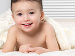 Portrait of a cute smiling two year old baby boy lying on a bed under a blanket