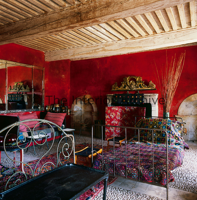 A bold red living room with a low beamed ceiling. The room is a riot of vibrant colour and pattern. Iron campaign beds provide seating and are covered with floral patterned wool blankets. The older furniture contrasts with plastic-topped 1950s tables. A floral screen stands in front of a fireplace.