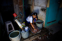 15 year old Nasridah, a student at Kartini Emergency School, washes clothes in the slum neigbourhood where she lives. Unable to continue her studies in her village due to economic constraints, Nasridah came to Jakarta in early 2007 to work as a domestic worker. She says, &quot;One day while I was watching the television, I saw news about the 'Twin Teachers' and their free emergency school. I was very excited and decided to look for the school. Upon meeting the twins I asked them if I could study there and they accepted me. Because I don't have a home in Jakarta, the twins found me a family in the slum area near the school who were willing to let me stay in their home for free in exchange for some household chores such as washing and ironing clothes. When I complete my high school study I would like to work in a Salon.&quot; Since the early 1990s, twin sisters Sri Rosyati (known as Rossy) and Sri Irianingsih (known as Rian) have used their family inheritance to set up and run 64 schools in different parts of Indonesia, providing primary education combined with practical skills to some of the country's most deprived children.