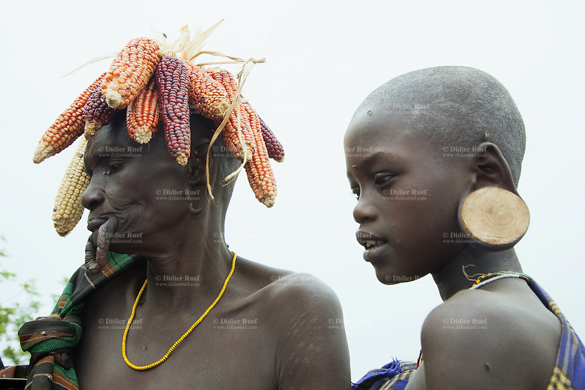 """Ethiopia. Southern Nations, Nationalities, and Peoples' Region. Omo Valley. Mursi tribe. Village and huts. Agro-pastoralist group. Nomadic. Two Mursi women. An elderly woman with maize on her head and  a teen women with a wooden earring. Mursi women are known as """"disk-lip"""" women. The bottom lip is slit along its full length and the front bottom row of teeth are pulled out to accomodate the ceramic disk which is handmade with a rim around which the stretched lip is pulled. The women are famed for wearing large plates in their lips (round clay plates placed into a cut in the lower lip) and ears. The disk is seen as a symbol of beauty and wealth, and often the younger girls will pierce and strech their ear-lobes, inserting a matching disk in the extended lobe. The Omo Valley, situated in Africa's Great Rift Valley, is home to an estimated 200,000 indigenous peoples who have lived there for millennia. Amongst them are 8'000 Mursi who dwell between the Omo and Mago rivers. Southern Nations, Nationalities, and Peoples' Region (often abbreviated as SNNPR) is one of the nine ethnic divisions of Ethiopia. 11.11.15 © 2015 Didier Ruef"""
