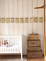 In a child's bedroom a pyramid of baskets is used for storage and the pages of a vintage school book have been turned into a frieze