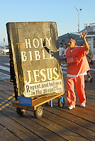 Christian Street Preacher Isidro Mendoza pushes his giant bible at the Santa Monica Pier on Sunday, Aug 19, 2012.