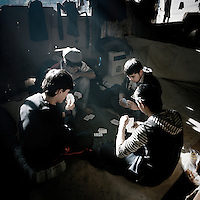 Young Afghan refugees play cards in an abandoned building where they squat. Patras is home to about 3,000 illegal immigrants. Most of them are Afghans, although there are also some Iranians and Uzbeks. They stop in Patras to try and find passage to various European destinations by hiding in ships, containers and trucks parked in the port. If they are lucky they will make it to their destination. Many of them live in shacks made from cartons, plastic and wood they found on the beach. To shelter from the cold they also squat in abandoned buildings, living without water and electricity. The living conditions are inhumane and unhygienic.